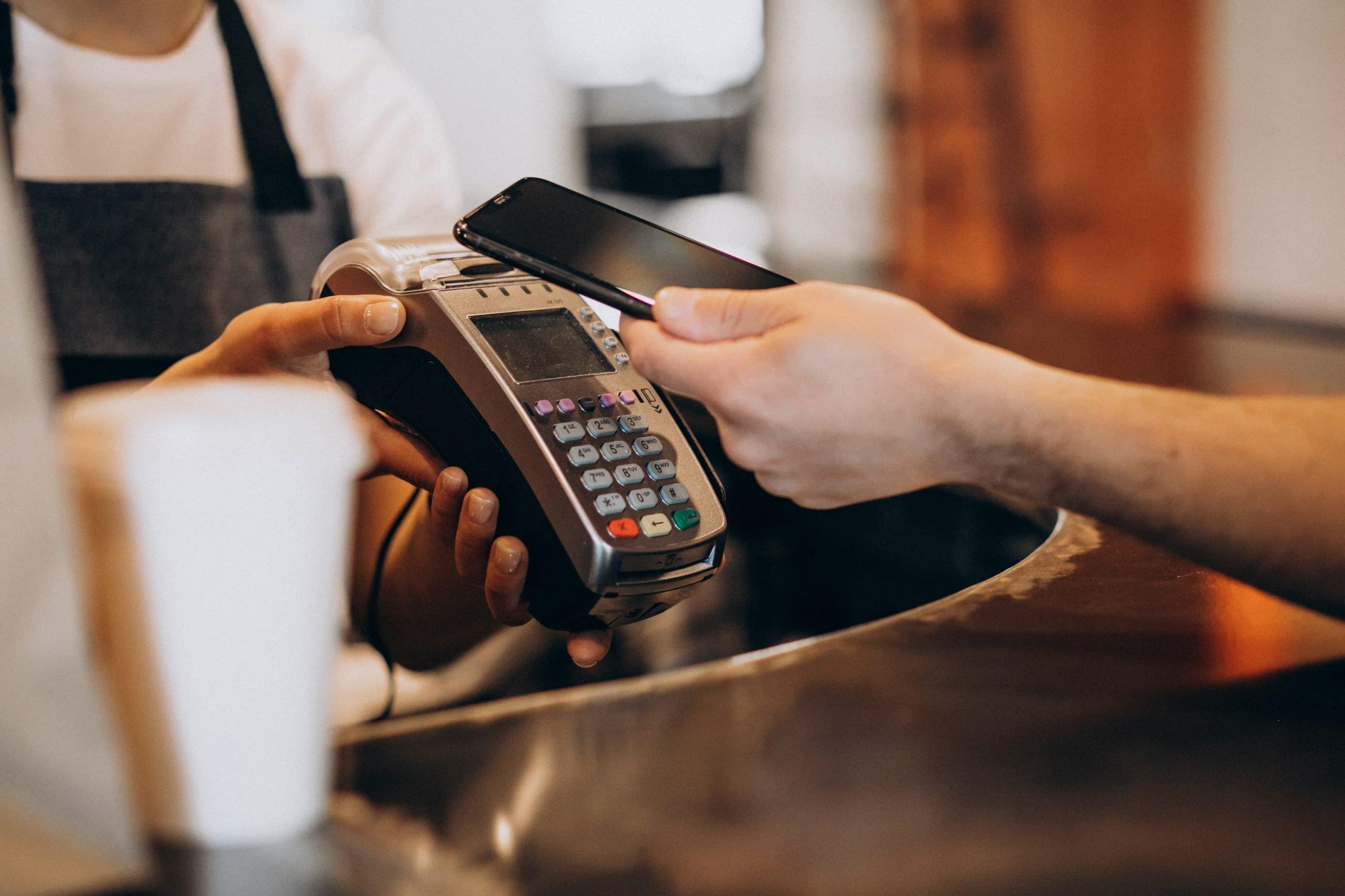 Homem paga com o celular na maquina de cartão